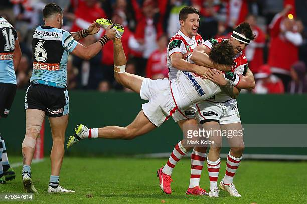 Jack Bird of the Sharks holds the leg of Mitch Rein of the Dragons as he celebrates with his team mates Gareth Widdop and Jake Marketo of the Dragons...