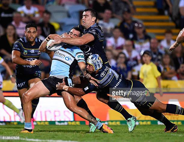 Jack Bird of the Sharks is tackled by Johnathan Thurston and Kane Linnett of the Cowboys during the round one NRL match between the North Queensland...
