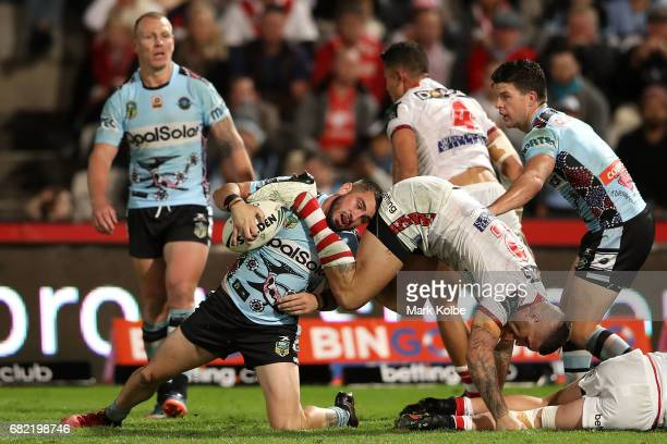 Jack Bird of the Sharks tries to get to his feet under pressure from Joel Thompson of the Dragons during the round 10 NRL match between the St George...