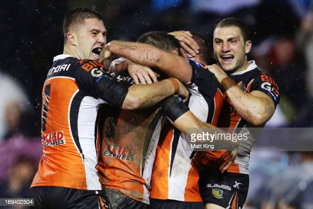 Jack Buchanan of the Tigers celebrates with Curtis Sironen and Robbie Farah during the round 11 NRL match between the Wests Tigers and the North...