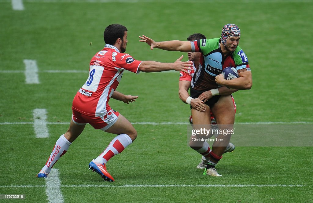 Jack Clifford of Harlequins is tackled by Matt Cox of Gloucester as he holds off Gareth Evans during the Cup Semi Final match between Gloucester and Harlequins in the World Club 7's at Twickenham Stadium on August 18, 2013 in London, England.