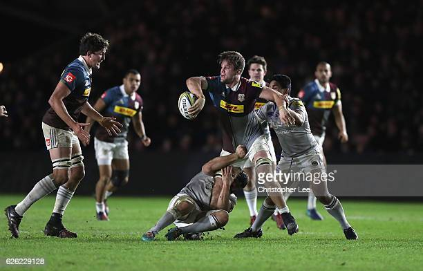 Jack Clifford of Quins passes the ball as he is tackled by Tom Ellis and Ben Tapuai of Bath during the Aviva Premiership match between Harlequins and...