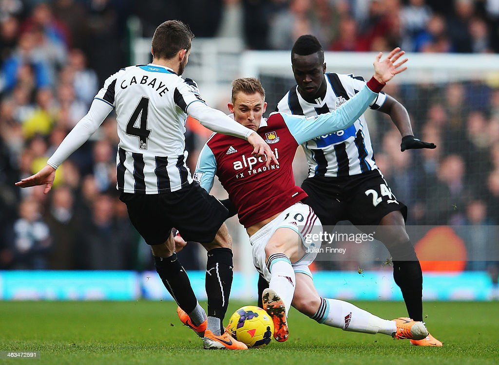 Jack Collison of West Ham United is challenged by Yohan Cabaye and Cheik Tiote of Newcastle United during the Barclays Premier League match between...