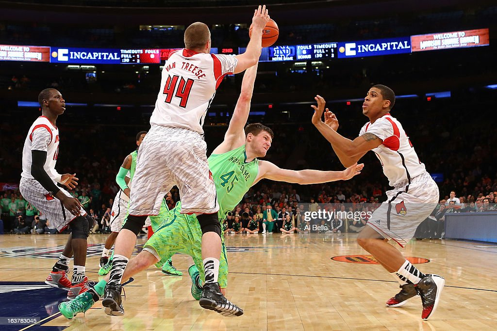 Jack Cooley #45 of the Notre Dame Fighting Irish falls as he fights for the ball against Stephan Van Treese #44 and Wayne Blackshear #20 of the Louisville Cardinals during the semifinals of the Big East Men's Basketball Tournament at Madison Square Garden on March 15, 2013 in New York City.