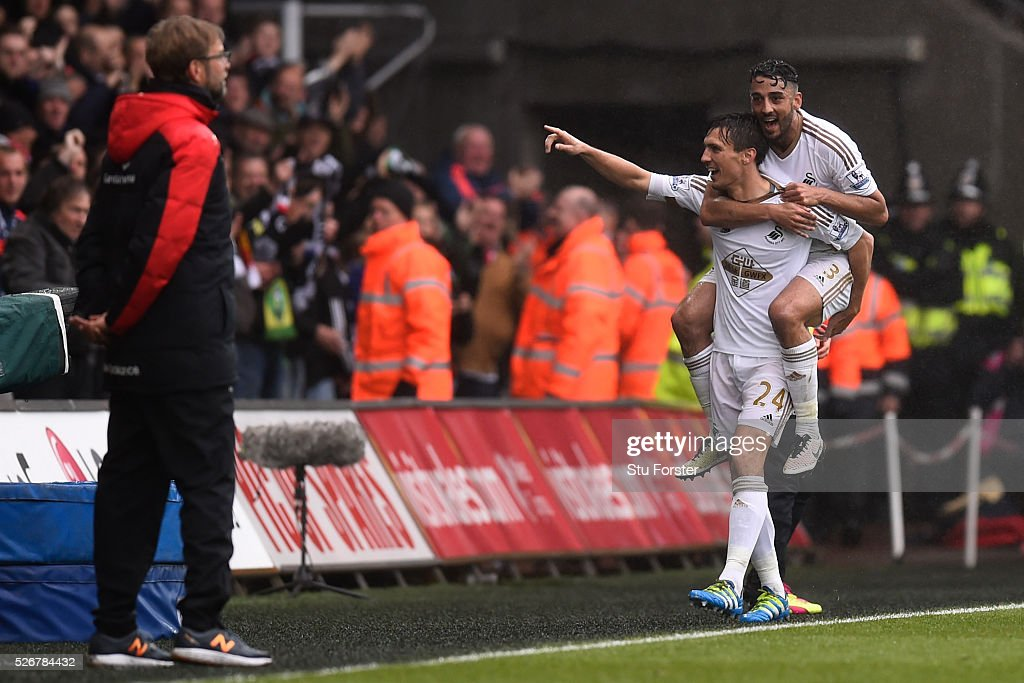 <a gi-track='captionPersonalityLinkClicked' href=/galleries/search?phrase=Jack+Cork&family=editorial&specificpeople=4206991 ng-click='$event.stopPropagation()'>Jack Cork</a> of Swansea City celebrates scoring his team's second goal with Neil Taylor as Jurgen Klopp, manager of Liverpool looks on during the Barclays Premier League match between Swansea City and Liverpool at The Liberty Stadium on May 1, 2016 in Swansea, Wales.