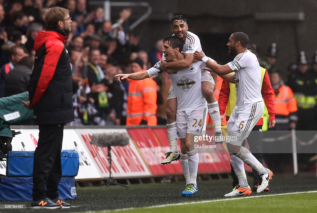 <a gi-track='captionPersonalityLinkClicked' href=/galleries/search?phrase=Jack+Cork&family=editorial&specificpeople=4206991 ng-click='$event.stopPropagation()'>Jack Cork</a> of Swansea City celebrates scoring his team's second goal with Neil Taylor and <a gi-track='captionPersonalityLinkClicked' href=/galleries/search?phrase=Ashley+Williams+-+Soccer+Player&family=editorial&specificpeople=13495389 ng-click='$event.stopPropagation()'>Ashley Williams</a> (R) as Jurgen Klopp, manager of Liverpool looks on during the Barclays Premier League match between Swansea City and Liverpool at The Liberty Stadium on May 1, 2016 in Swansea, Wales.