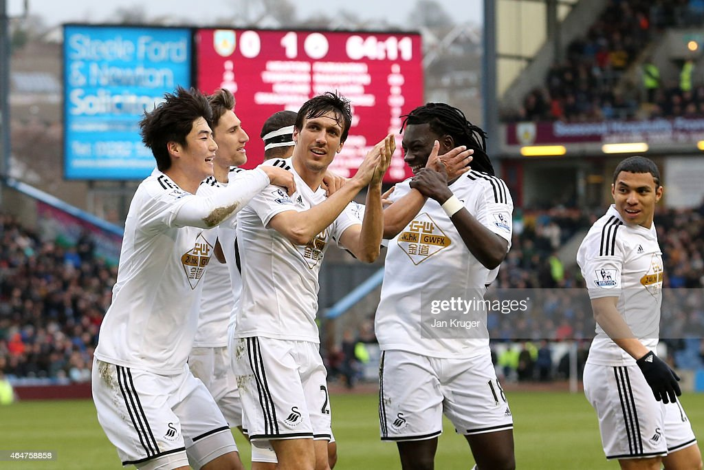 Jack Cork (C) of Swansea City is congratulated by teamates after his shot is deflected for an own goal during the Barclays Premier League match between Burnley and Swansea City at Turf Moor on February 28, 2015 in Burnley, England.