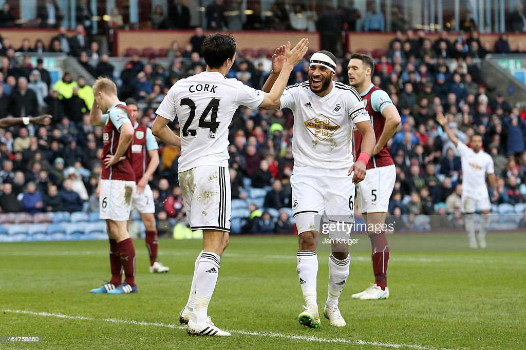 <a gi-track='captionPersonalityLinkClicked' href=/galleries/search?phrase=Jack+Cork&family=editorial&specificpeople=4206991 ng-click='$event.stopPropagation()'>Jack Cork</a> #24 of Swansea City is congratulated by teammate <a gi-track='captionPersonalityLinkClicked' href=/galleries/search?phrase=Ashley+Williams+-+Fu%C3%9Fballspieler&family=editorial&specificpeople=13495389 ng-click='$event.stopPropagation()'>Ashley Williams</a> of Swansea City after his shot is deflected for an own goal during the Barclays Premier League match between Burnley and Swansea City at Turf Moor on February 28, 2015 in Burnley, England.
