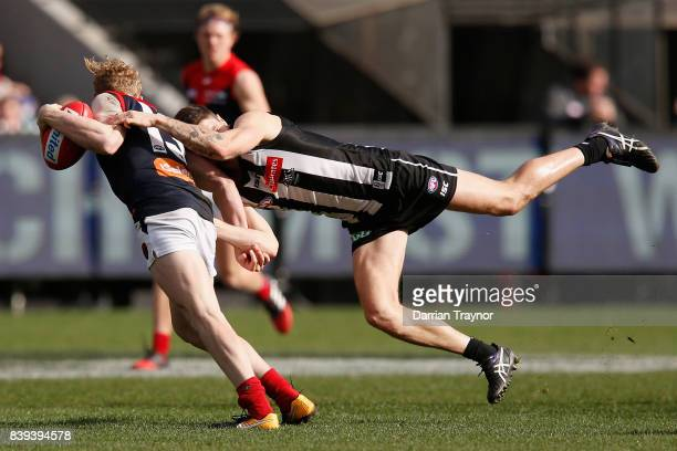 Jack Crisp of the Magpies tackles Clayton Oliver of the Demons during the round 23 AFL match between the Collingwood Magpies and the Melbourne Demons...