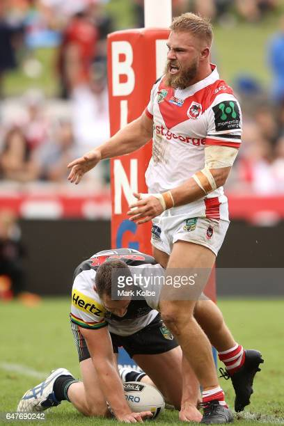 Jack de Belin of the Dragons celebrates scoring a try as Isaah Yeo of the Panthers looks dejected during the round one NRL match between the St...