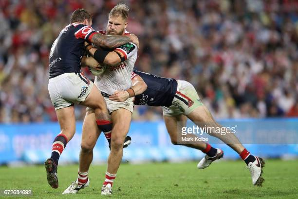 Jack de Belin of the Dragons is tackled by Jake Friend and Kane Evans of the Roosters during the round eight NRL match between the Sydney Roosters...