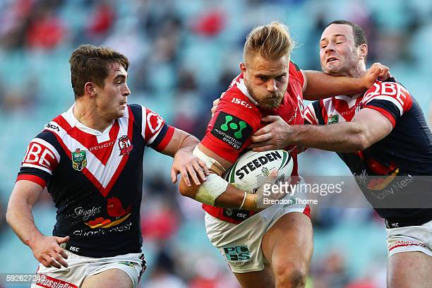 Jack De Belin of the Dragons is tackled by Roosters defence during the round 24 NRL match between the Sydney Roosters and the St George Illawarra...