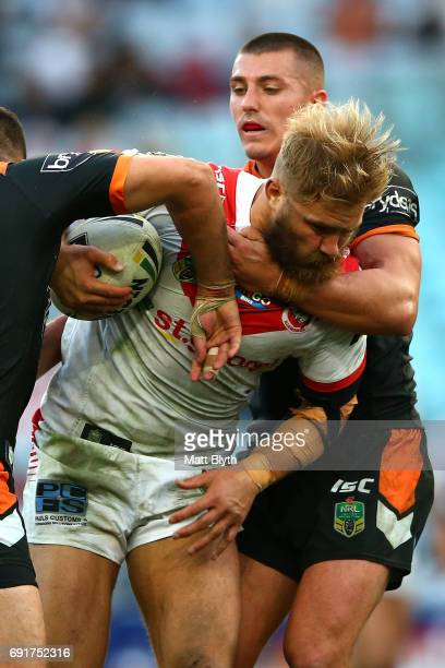 Jack de Belin of the Dragons is tackled during the round 13 NRL match between the St George Illawarra Dragons and the Wests Tigers at ANZ Stadium on...