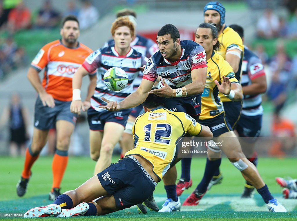 Jack Debreczeni of the Rebels passes the ball whilst being tackled by Christian Lealiifano of the Brumbies during the round three Super Rugby match...