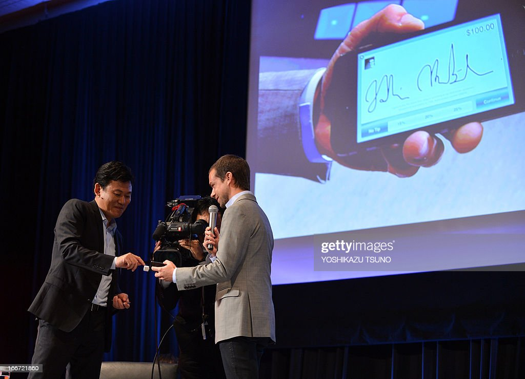 Jack Dorsey (C), Chairman of Twitter and CEO of Square demonstrates an online transaction, while Rakurten president Hiroshi Mikitani (L) gives his signature on a smartphone during a conference of the New Economy Summit 2013 in Tokyo on April 16, 2013.a Entrepreneurs of information technology (IT) and online business on April 16 gathered at a one-day conference, hosted by Japan Association of New Economy (JANE), led by Japanese electronic commerce giant Rakuten's Hiroshi Mikitani. AFP PHOTO / Yoshikazu TSUNO