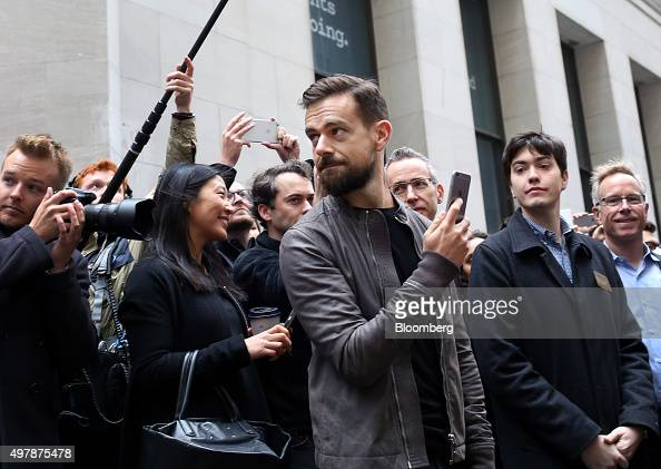 Jack Dorsey chief executive officer of Square Inc center holds an Apple Inc iPhone while standing outside of the New York Stock Exchange in New York...