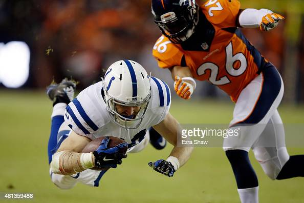Jack Doyle of the Indianapolis Colts dives after a catch as Rahim Moore of the Denver Broncos covers the play during a 2015 AFC Divisional Playoff...