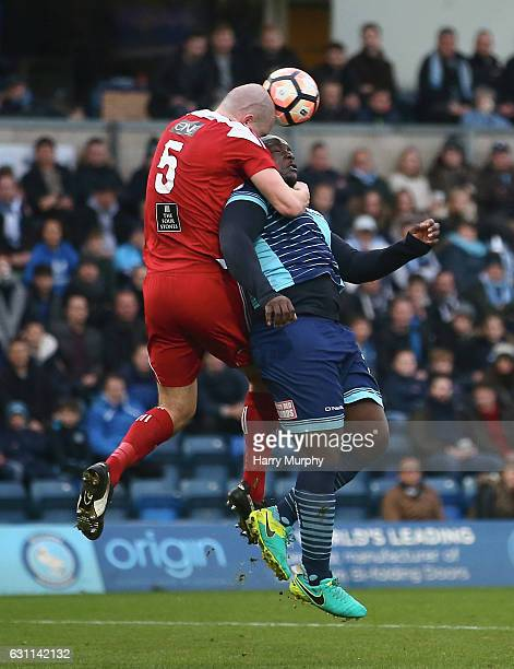 Jack Duggan of Stourbridge and Adebayo Akinfenwa of Wycome Wanderers challenge for the ball during The Emirates FA Cup Third Round match between...