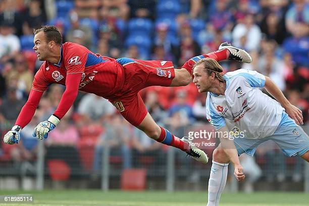 Jack Duncan of the Jets punches the ball in front of Rhyan Grant of Sydney FC during the round four ALeague match between the Newcastle jets and...