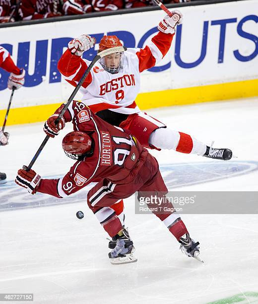 Jack Eichel of the Boston University Terriers checks Jake Horton of the Harvard Crimson during NCAA hockey in the semifinals of the annual Beanpot...