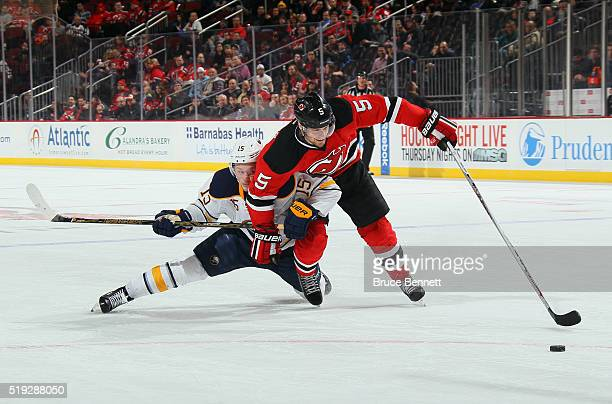 Jack Eichel of the Buffalo Sabres and Adam Larsson of the New Jersey Devils battle for the puck during the third period at the Prudential Center on...