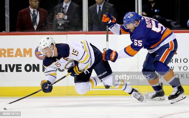 Jack Eichel of the Buffalo Sabres and Johnny Boychuk of the New York Islanders chase the puck during the third period at Barclays Center on October 7...