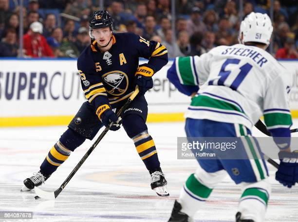 Jack Eichel of the Buffalo Sabres bring the puck into the zone as Troy Stecher of the Vancouver Canucks defends during the second period at the...