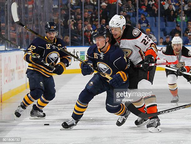 Jack Eichel of the Buffalo Sabres gets checked by Mike Santorelli of the Anaheim Ducks during an NHL game on December 17 2015 at the First Niagara...