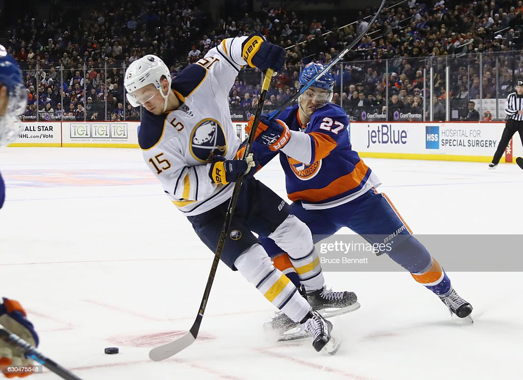 Jack Eichel #15 of the Buffalo Sabres is checked by Anders Lee #27 of the New York Islanders during the first period at the Barclays Center on December 23, 2016 in the Brooklyn borough of New York City.