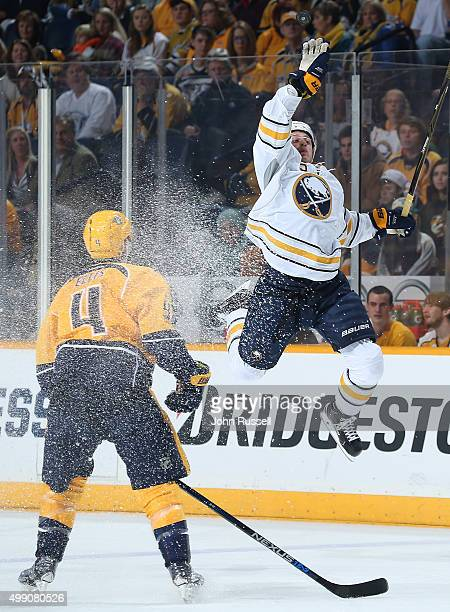 Jack Eichel of the Buffalo Sabres leaps for the puck against Ryan Ellis of the Nashville Predators during an NHL game at Bridgestone Arena on...