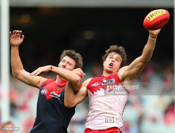 Jack Fitzpatrick of the Demons and Mike Pyke of the Swans compete for the ball during the round 15 AFL match between the Melbourne Demons and the...