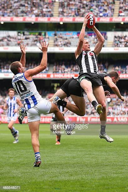 Jack Frost of the Magpies marks the ball against Ben Cunnington of the Kangaroos and teamate Nick Maxwell during the round five AFL match between the...