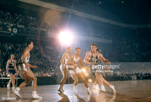 Jack George of the Philadelphia Warriors dribbles the ball as he is defended by Larry Friend and Carl Braun of the New York Knicks during an NBA game...
