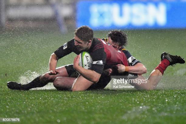 Jack Goodhue of the Crusaders is tackled by Richard Buckman of the Highlanders during the Super Rugby Quarter Final match between the Crusaders and...