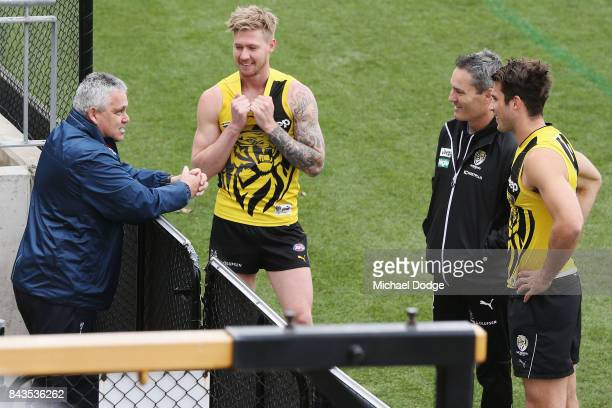 Jack Graham and Alex Rance of the Tigers greet fromer assistant coach Mark Wiliams during a Richmond Tigers AFL training session at Punt Road Oval on...