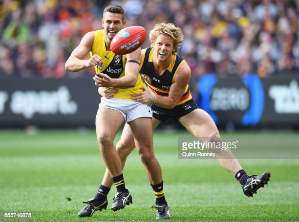 Jack Graham of the Tigers handballs whilst being tackled by Rory Sloane of the Crows during the 2017 AFL Grand Final match between the Adelaide Crows...
