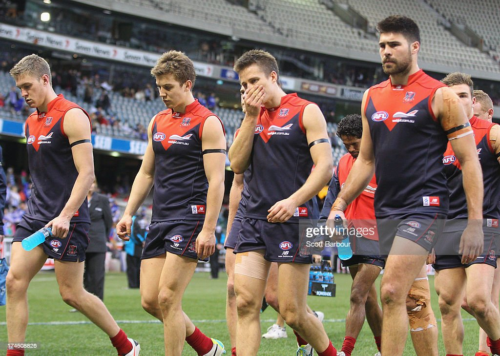 Jack Grimes and the Demons leave the field after losing the round 18 AFL match between the Melbourne Demons and the North Melbourne Kangaroos at Etihad Stadium on July 27, 2013 in Melbourne, Australia.