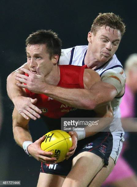 Jack Grimes of the Demons is tackled by Colin Sylvia of the Dockers during the round 16 AFL match between the Melbourne Demons and the Fremantle...