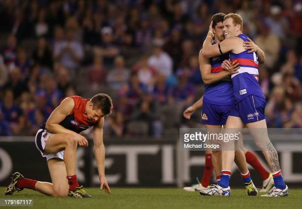 Jack Grimes of the Demons reacts as Tom Liberatore and Adam Cooney of the Bulldogs celebrate a goal during the round 23 AFL match between the Western...