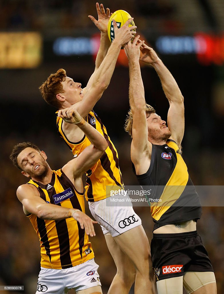 Jack Gunston and Tim O'Brien of the Hawks compete for the ball against Kamdyn McIntosh of the Tigers during the 2016 AFL Round 07 match between the Richmond Tigers and the Hawthorn Hawks at the Melbourne Cricket Ground, Melbourne on May 6, 2016.
