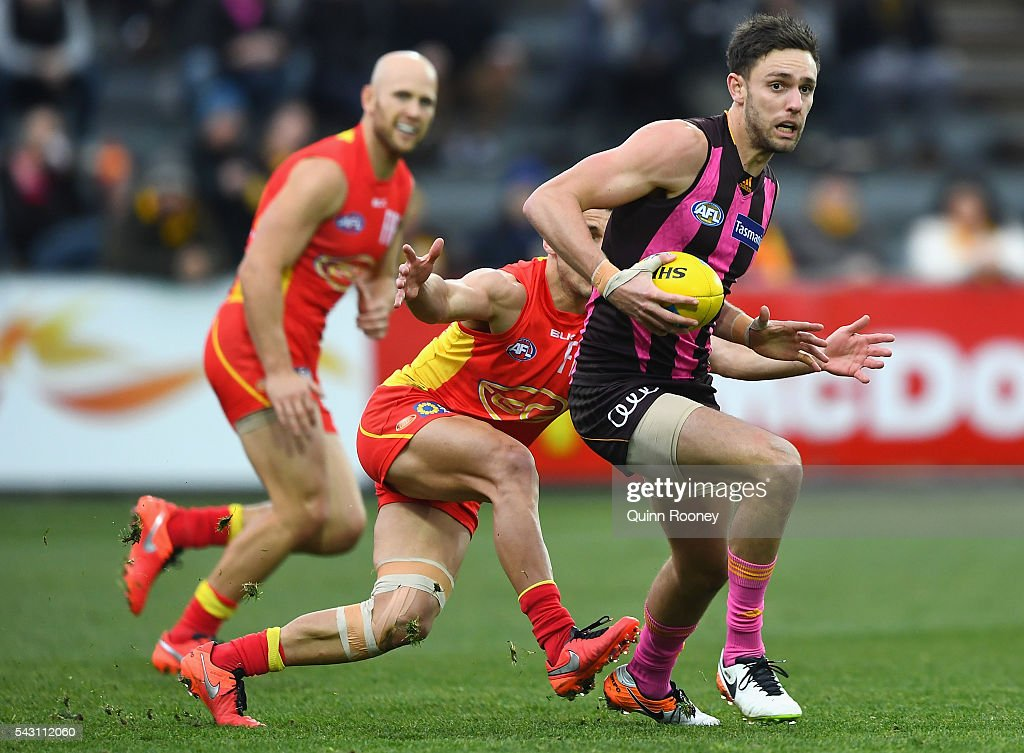 Jack Gunston of the Hawks avoids a tackle by Dion Prestia of the Suns during the round 14 AFL match between the Hawthorn Hawks and the Gold Coast Suns at Aurora Stadium on June 26, 2016 in Launceston, Australia.