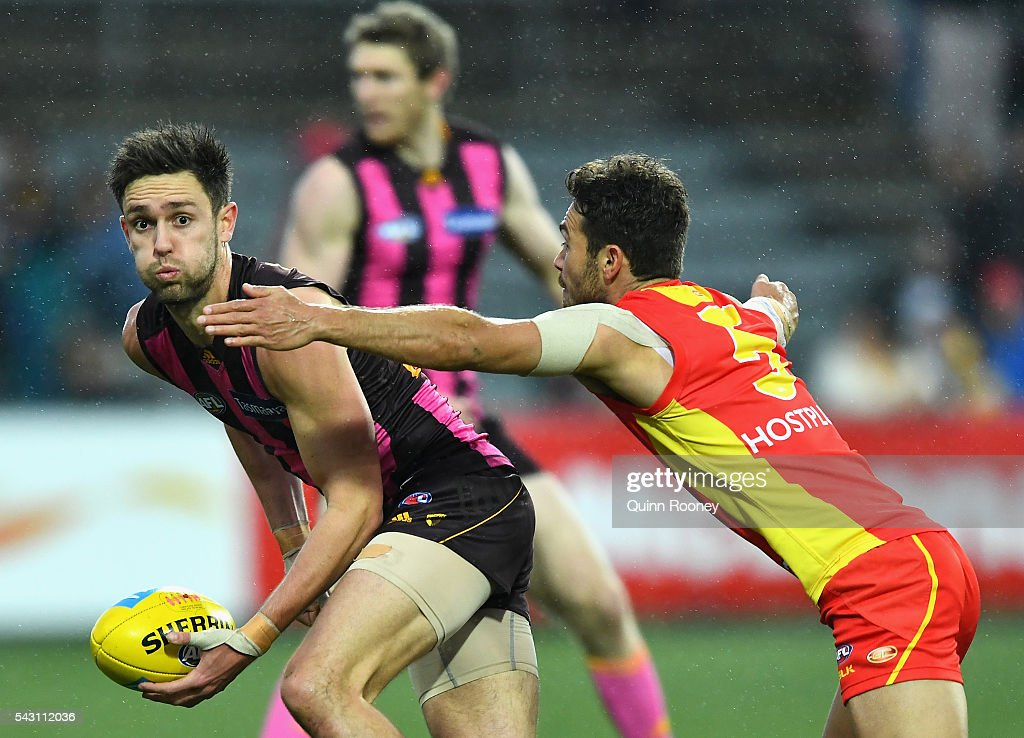 Jack Gunston of the Hawks handballs whilst being tackled by Jarrod Harbrow of the Suns during the round 14 AFL match between the Hawthorn Hawks and the Gold Coast Suns at Aurora Stadium on June 26, 2016 in Launceston, Australia.
