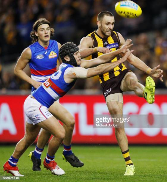 Jack Gunston of the Hawks kicks the ball away from Caleb Daniel of the Bulldogs during round 23 AFL match between the Hawthorn Hawks and the Western...