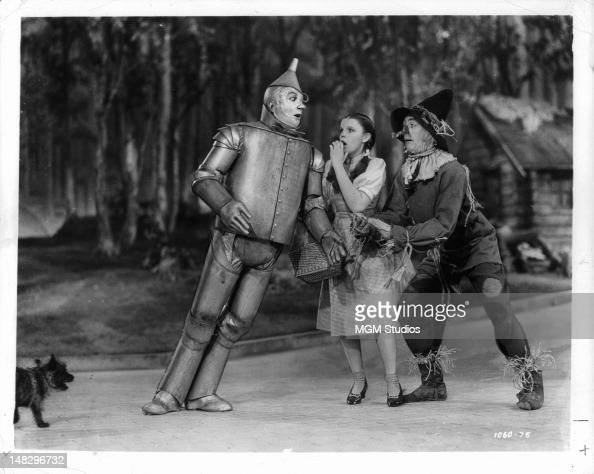 Jack Haley as the Tin Man leans toward Judy Garland and Ray Bolger as the Scarecrow while on the Yellow Brick Road as Toto tags along in a scene from...