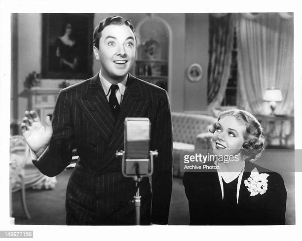 Jack Haley standing before mic as Alice Faye watches in a scene from the film 'Wake Up And Live' 1937