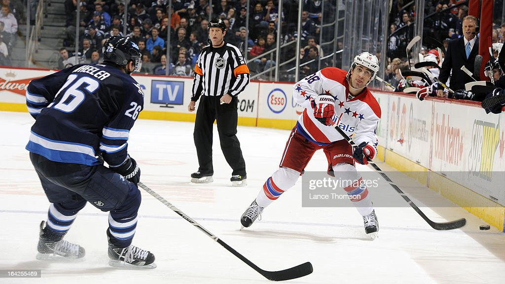 <a gi-track='captionPersonalityLinkClicked' href=/galleries/search?phrase=Jack+Hillen&family=editorial&specificpeople=5088928 ng-click='$event.stopPropagation()'>Jack Hillen</a> #38 of the Washington Capitals plays the puck along the boards as <a gi-track='captionPersonalityLinkClicked' href=/galleries/search?phrase=Blake+Wheeler&family=editorial&specificpeople=716703 ng-click='$event.stopPropagation()'>Blake Wheeler</a> #26 of the Winnipeg Jets defends during third-period action at the MTS Centre on March 21, 2013 in Winnipeg, Manitoba, Canada.