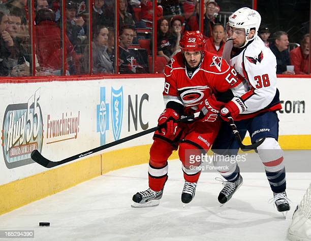 Jack Hillen of the Washington Capitals slows Chad LaRose of the Carolina Hurricanes as he carries the puck behind the net during their NHL game at...