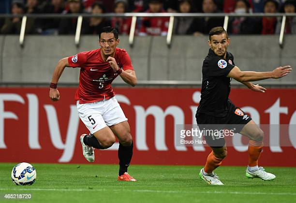 Jack Hingert of Brisbane Roar and Tomoaki Makino of Urawa Red Diamonds compete for the ball during the AFC Champions League Group G match between...
