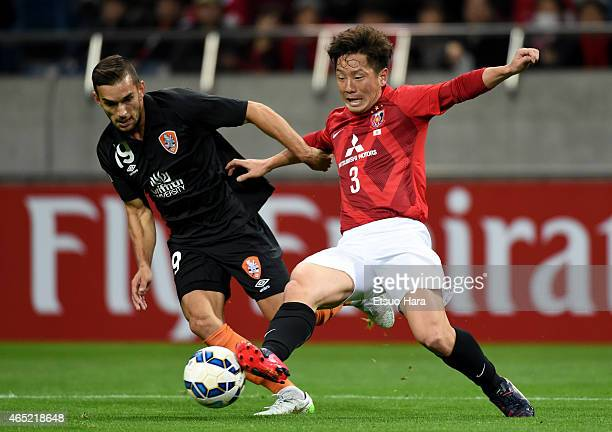 Jack Hingert of Brisbane Roar and Tomoya Ugajin of Urawa Red Diamonds compete for the ball during the AFC Champions League Group G match between...