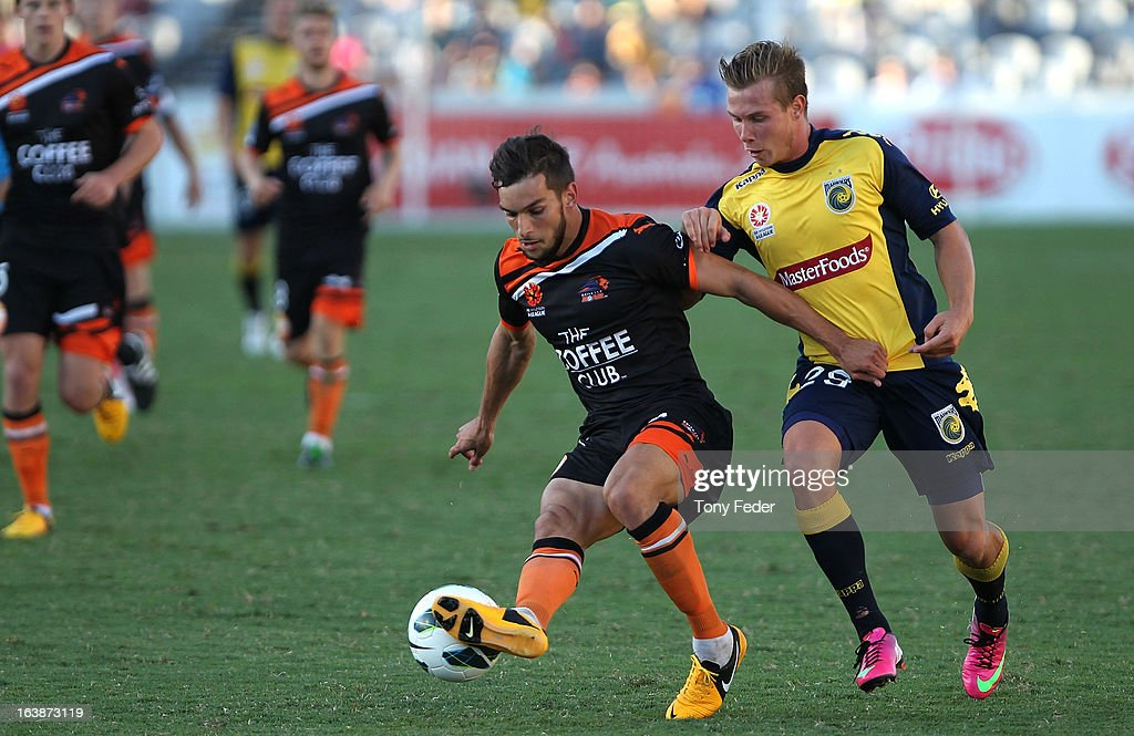 Jack Hingert of Brisbane Roar controls the ball in front of Nick Fitzgerald of the Mariners during the round 25 A-League match between the Central Coast Mariners and the Brisbane Roar at Bluetongue Stadium on March 17, 2013 in Gosford, Australia.
